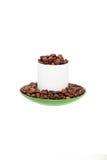 Άσπρο κεραμικό φλυτζάνι που γεμίζουν με τα φασόλια καφέ Στοκ Φωτογραφίες