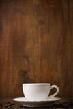 Άσπρο κεραμικό φλυτζάνι στο άσπρο πιατάκι στο ξύλινο υπόβαθρο Στοκ Φωτογραφία