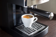 Άσπρο κεραμικό φλυτζάνι του espresso με τη μηχανή καφέ Στοκ Εικόνες