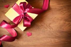 Άσπρο κιβώτιο δώρων και κόκκινη κορδέλλα με την ετικέττα στο ξύλινο υπόβαθρο Εκλεκτής ποιότητας κιβώτιο δώρων στον ξύλινο πίνακα  στοκ φωτογραφίες