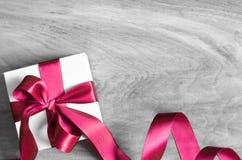 Άσπρο κιβώτιο δώρων και κόκκινη κορδέλλα με την ετικέττα στο ξύλινο υπόβαθρο Εκλεκτής ποιότητας κιβώτιο δώρων στον ξύλινο πίνακα  στοκ εικόνα