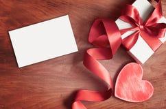 Άσπρο κιβώτιο δώρων και κόκκινη κορδέλλα με την ετικέττα στο ξύλινο υπόβαθρο Εκλεκτής ποιότητας κιβώτιο δώρων στον ξύλινο πίνακα  στοκ φωτογραφία με δικαίωμα ελεύθερης χρήσης