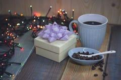 Άσπρο κιβώτιο δώρων, μπλε φλυτζάνι, φασόλια καφέ στο μπλε pialn Στοκ Εικόνα