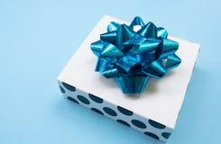 Άσπρο κιβώτιο δώρων σχεδίων σημείων Πόλκα σε ένα μπλε υπόβαθρο, που διακοσμείται με ένα μπλε τόξο, που δημιουργεί μια ρομαντική α στοκ εικόνες με δικαίωμα ελεύθερης χρήσης