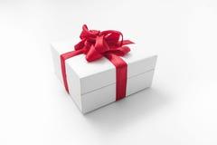 Άσπρο κιβώτιο με ένα κόκκινο δώρο τόξων Στοκ Φωτογραφία