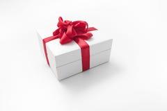 Άσπρο κιβώτιο με ένα κόκκινο δώρο τόξων Στοκ Φωτογραφίες