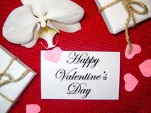 Άσπρο κιβώτιο ορχιδεών και δώρων σε ένα κόκκινο υπόβαθρο, υπόβαθρο ημέρας βαλεντίνων Μικρές καρδιές εγγράφου στοκ εικόνα με δικαίωμα ελεύθερης χρήσης