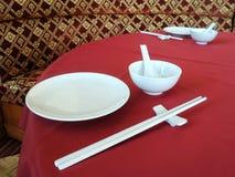Άσπρο κινεζικό επιτραπέζιο σκεύος στο κόκκινο επιτραπέζιο ύφασμα Στοκ Εικόνες
