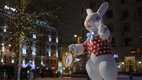 Άσπρο κουνέλι με το ρολόι τσεπών στη διακοσμημένη οδό στην πόλη απόθεμα βίντεο
