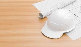 Άσπρο κράνος ασφάλειας στον ξύλινο πίνακα με τα σχεδιαγράμματα Κράνος ασφάλειας για τους μηχανικούς, τους επόπτες, τους διευθυντέ στοκ εικόνες με δικαίωμα ελεύθερης χρήσης