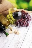 Άσπρο κρασί και κόκκινο κρασί σε ένα γυαλί με τα σταφύλια πτώσης, άσπρο woode Στοκ φωτογραφίες με δικαίωμα ελεύθερης χρήσης