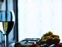Άσπρο κρασί σε ένα γυαλί με τα ορεκτικά σε έναν ξύλινο πίνακα, ένα καθορισμένο ο Στοκ Φωτογραφίες