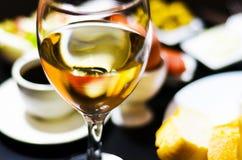 Άσπρο κρασί σε ένα γυαλί με τα ορεκτικά σε έναν ξύλινο πίνακα, ένα καθορισμένο ο Στοκ Εικόνα