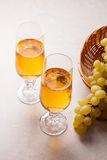 άσπρο κρασί σταφυλιών Άσπρο κρασί στα γυαλιά και τα σταφύλια στο φως Στοκ φωτογραφίες με δικαίωμα ελεύθερης χρήσης