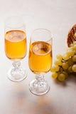 άσπρο κρασί σταφυλιών Άσπρο κρασί στα γυαλιά και τα σταφύλια στο φως Στοκ φωτογραφία με δικαίωμα ελεύθερης χρήσης