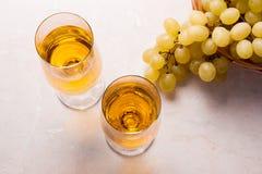 άσπρο κρασί σταφυλιών Άσπρο κρασί στα γυαλιά και τα σταφύλια στο φως Στοκ Φωτογραφίες