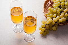 άσπρο κρασί σταφυλιών Άσπρο κρασί στα γυαλιά και τα σταφύλια στο φως Στοκ Εικόνα
