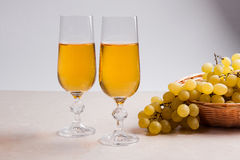 άσπρο κρασί σταφυλιών Άσπρο κρασί στα γυαλιά και τα σταφύλια στο φως Στοκ Εικόνες