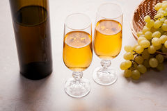 άσπρο κρασί σταφυλιών Άσπρο κρασί στα γυαλιά, μπουκάλι του κρασιού και Στοκ Φωτογραφίες