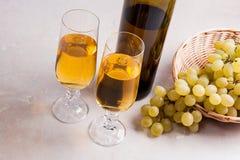 άσπρο κρασί σταφυλιών Άσπρο κρασί στα γυαλιά, μπουκάλι του κρασιού και Στοκ Εικόνες