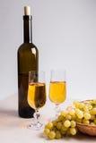 άσπρο κρασί σταφυλιών Άσπρο κρασί στα γυαλιά, μπουκάλι του κρασιού και Στοκ εικόνα με δικαίωμα ελεύθερης χρήσης