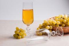 άσπρο κρασί σταφυλιών Άσπρο κρασί στο γυαλί και σταφύλια στο ελαφρύ μ Στοκ φωτογραφίες με δικαίωμα ελεύθερης χρήσης