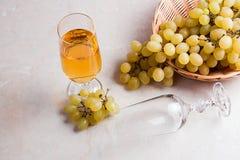 άσπρο κρασί σταφυλιών Άσπρο κρασί στο γυαλί και σταφύλια στο ελαφρύ μ Στοκ Εικόνα