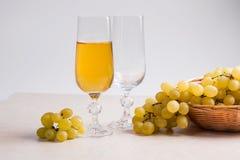 άσπρο κρασί σταφυλιών Άσπρο κρασί στο γυαλί και σταφύλια στο ελαφρύ μ Στοκ εικόνες με δικαίωμα ελεύθερης χρήσης