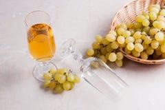 άσπρο κρασί σταφυλιών Άσπρο κρασί στο γυαλί και σταφύλια στο ελαφρύ μ Στοκ φωτογραφία με δικαίωμα ελεύθερης χρήσης