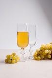 άσπρο κρασί σταφυλιών Άσπρο κρασί στο γυαλί και σταφύλια στο ελαφρύ μ Στοκ Εικόνες