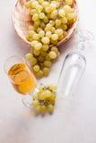 άσπρο κρασί σταφυλιών Άσπρο κρασί στο γυαλί και σταφύλια στο ελαφρύ μ Στοκ Φωτογραφία