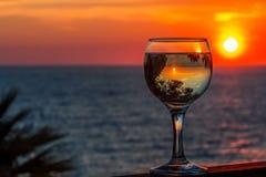 Άσπρο κρασί στο υπόβαθρο θάλασσας ηλιοβασιλέματος Στοκ εικόνες με δικαίωμα ελεύθερης χρήσης