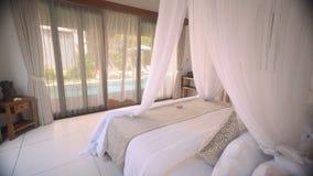 Άσπρο κρεβάτι θόλων στο δωμάτιο με την άποψη πισινών απόθεμα βίντεο