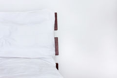 Άσπρο κρεβάτι με τα σεντόνια στο ξύλινο κρεβάτι που απομονώνεται στο άσπρο υπόβαθρο Στοκ εικόνα με δικαίωμα ελεύθερης χρήσης