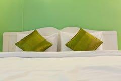 Άσπρο κρεβάτι στο πράσινο δωμάτιο Στοκ φωτογραφία με δικαίωμα ελεύθερης χρήσης