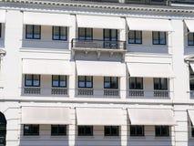 Άσπρο κτήριο με τις άσπρες καλύψεις ήλιων στοκ φωτογραφίες με δικαίωμα ελεύθερης χρήσης