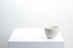 Άσπρο κύπελλο στον άσπρο πίνακα Στοκ Φωτογραφίες