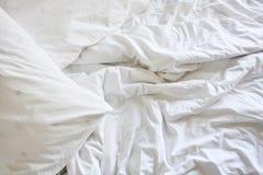 Άσπρο μαξιλάρι στο κρεβάτι και με το ακατάστατο κάλυμμα ρυτίδων στην κρεβατοκάμαρα Στοκ φωτογραφία με δικαίωμα ελεύθερης χρήσης