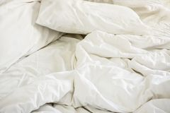 Άσπρο μαξιλάρι στο κρεβάτι και με το ακατάστατο κάλυμμα ρυτίδων στην κρεβατοκάμαρα Στοκ Εικόνες