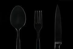 Άσπρο μαχαίρι κουταλιών δικράνων περιγράμματος στο μαύρο υπόβαθρο Στοκ Εικόνα