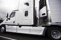 Άσπρο μεγάλο ημι φορτηγό εγκαταστάσεων γεώτρησης με το ημι ρυμουλκό σημαιοφόρων και refrigerat Στοκ εικόνα με δικαίωμα ελεύθερης χρήσης