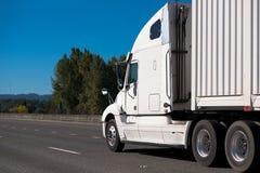 Άσπρο μεγάλο ημι φορτηγό εγκαταστάσεων γεώτρησης που μεταφέρει το εμπορευματοκιβώτιο κατά μήκος ευρύ διά Στοκ Φωτογραφίες