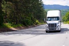 Άσπρο μεγάλο ημι φορτηγό εγκαταστάσεων γεώτρησης με την οδήγηση ρυμουλκών από ευρύ πολλαπλών γραμμών Στοκ Φωτογραφία