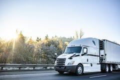 Άσπρο μοντέρνο μεγάλο ημι φορτηγό εγκαταστάσεων γεώτρησης που μεταφέρει το φθαρτό φορτίο στο ημι φορτηγό ψυγείων που τρέχει στο χ στοκ εικόνα με δικαίωμα ελεύθερης χρήσης