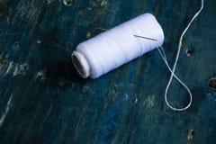 Άσπρο νήμα και ράβοντας βελόνα στο αγροτικό μπλε υπόβαθρο με το διάστημα για το κείμενο Ελάχιστα ράβοντας εργαλεία Στοκ Εικόνα