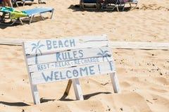 Άσπρο ξύλινο σημάδι στην παραλία, με το σημάδι: Οι κανόνες παραλιών - υπόλοιπο, χαλαρώνουν, επαναφορτίζουν και καλωσορίζουν στην  στοκ εικόνα