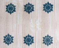Άσπρο ξύλινο υπόβαθρο με τις μπλε snowflake διακοσμήσεις Στοκ Εικόνες