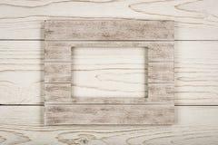 Άσπρο ξύλινο πλαίσιο για την εικόνα στο ξύλινο υπόβαθρο Στοκ εικόνες με δικαίωμα ελεύθερης χρήσης
