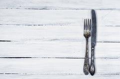 Άσπρο ξύλινο υπόβαθρο με τα μαχαιροπήρουνα Στοκ Εικόνα