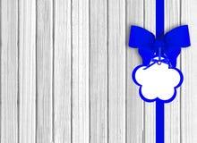 Άσπρο ξύλινο υπόβαθρο με το όμορφο μπλε τόξο με την ετικέττα Στοκ φωτογραφία με δικαίωμα ελεύθερης χρήσης